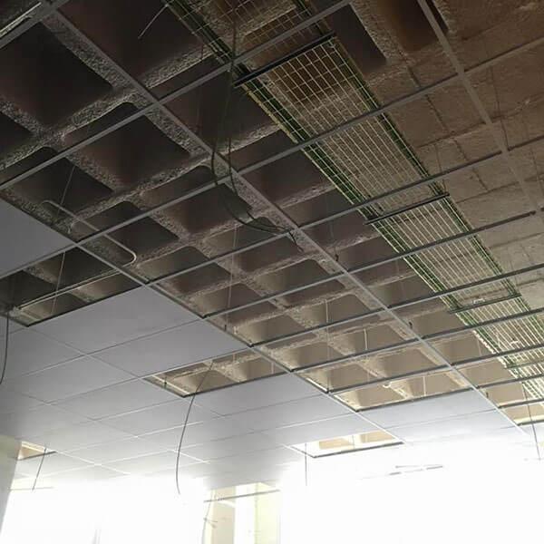 fotografía en la que se muestra la instalación de un falso techo por debajo de un techo de hormigón armado